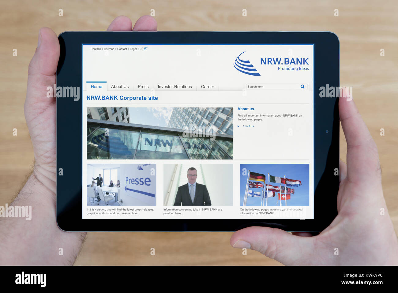 A man looks at the NRW.Bank website on his iPad tablet device, over a wooden table top background (Editorial use - Stock Image