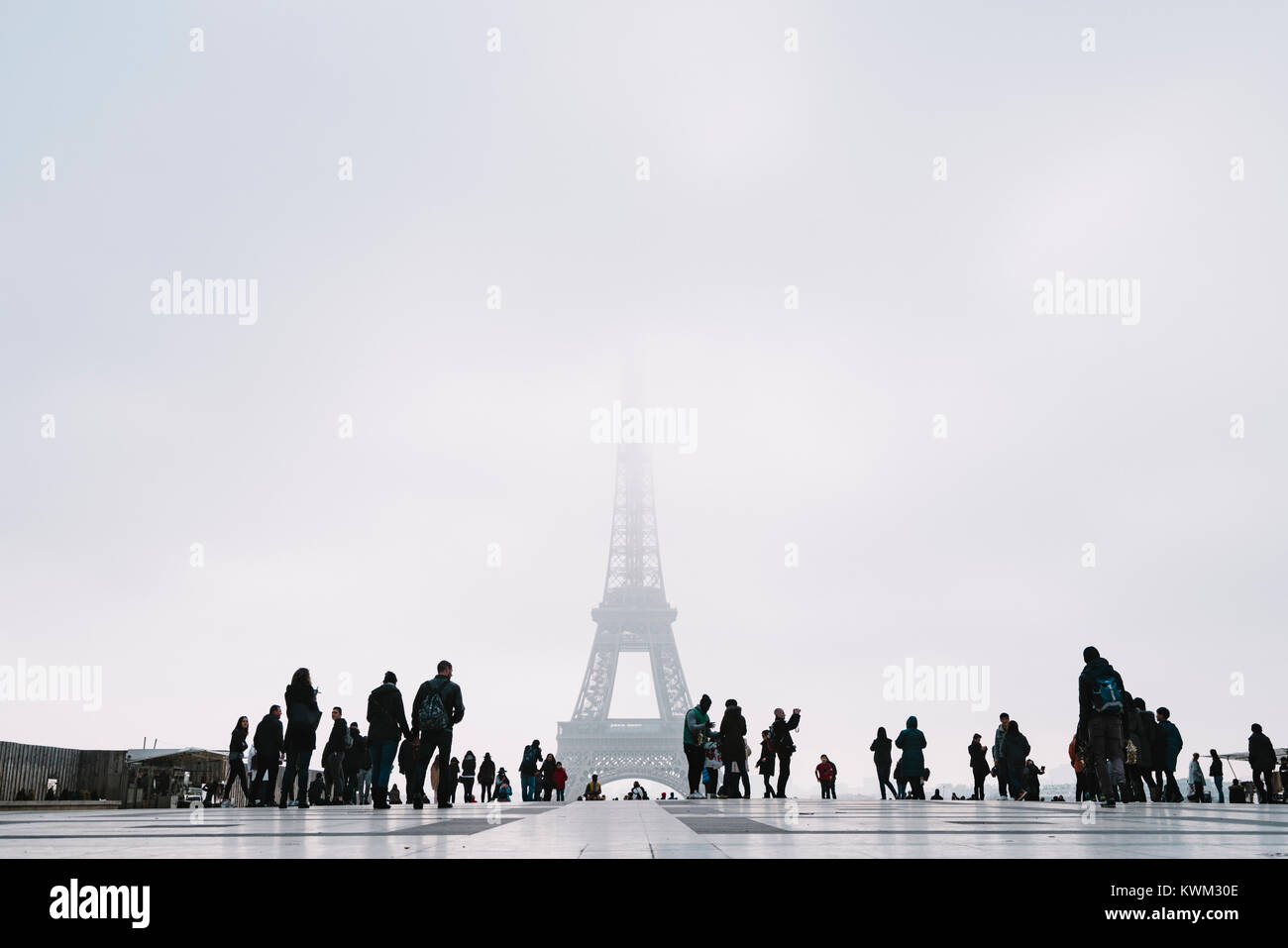 Low angle View of Eiffel tower against clear sky with tourists in foreground during foggy weather - Stock Image