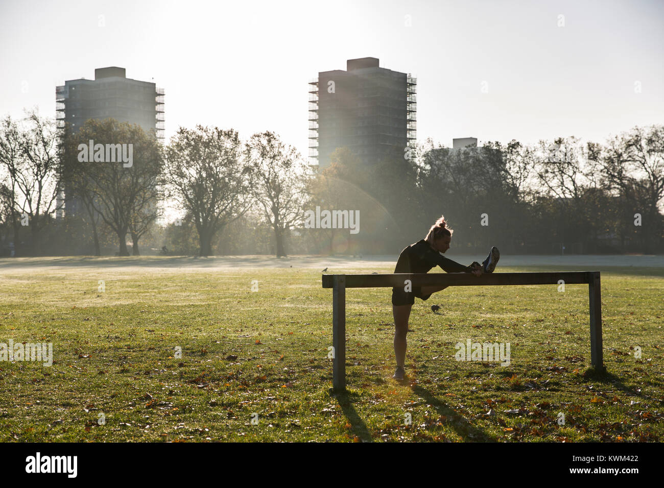 Full length of woman stretching leg on exercise equipment against buildings at park during sunny day - Stock Image