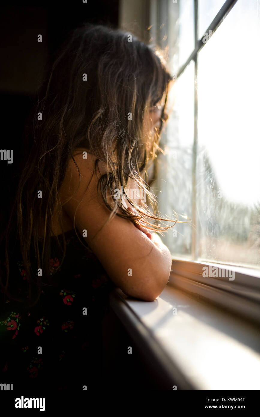 Side view of thoughtful girl looking though window at home - Stock Image