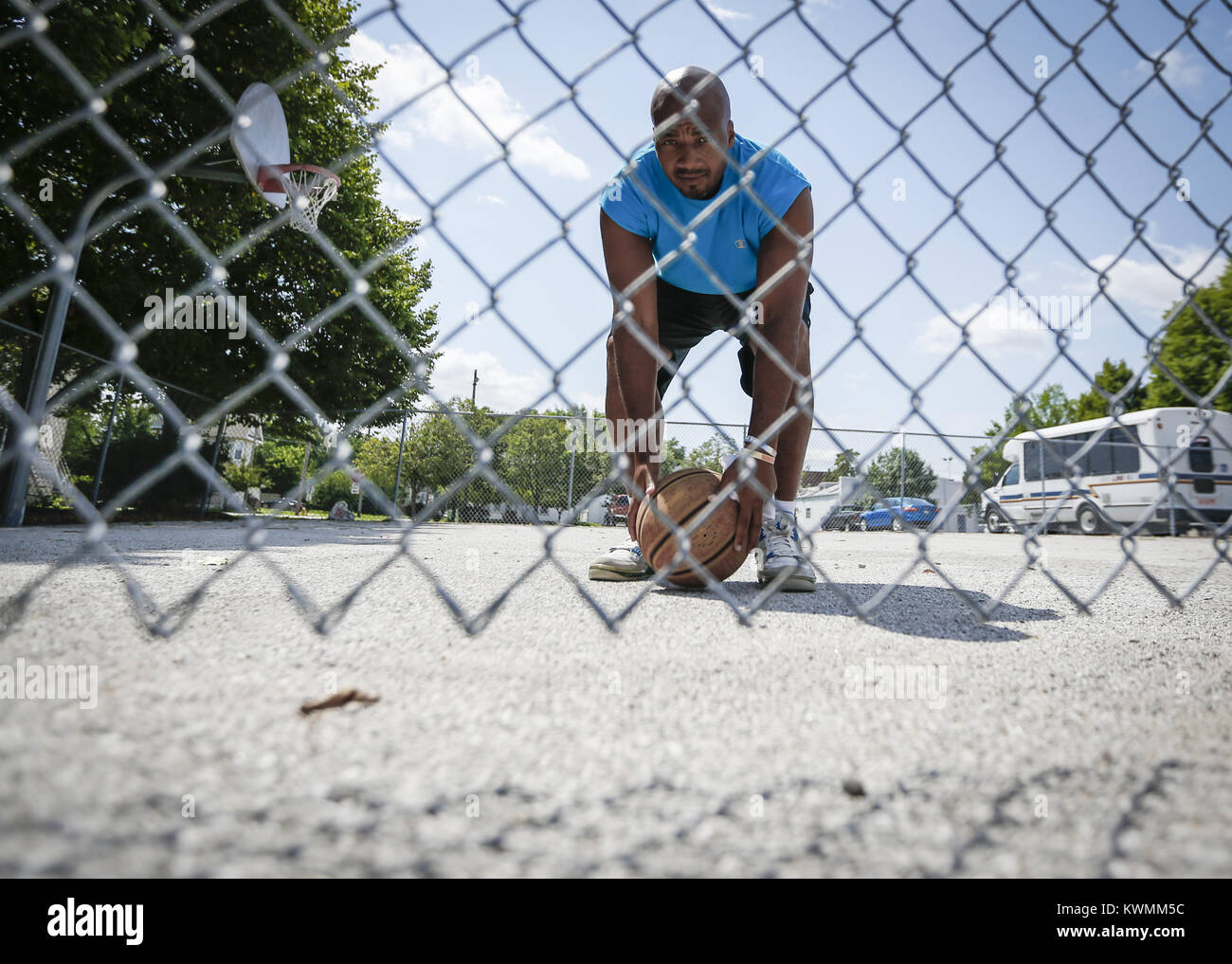 Davenport, Iowa, USA. 5th Aug, 2016. LeShawn Townsend bends down to retrieve his basketball while working out alone - Stock Image
