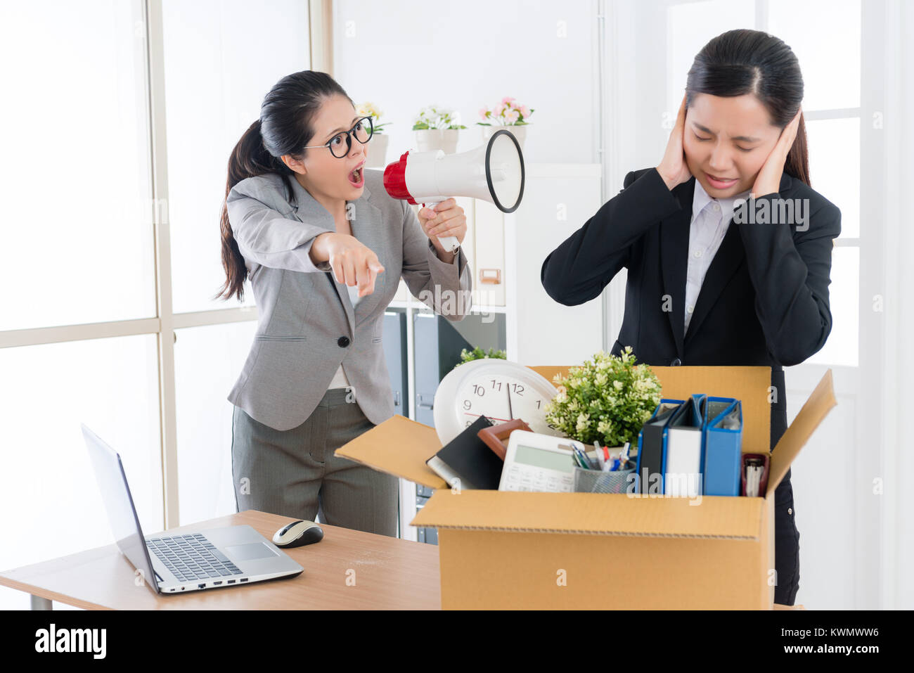pretty attractive female boss speaking with young beauty girl business worker and using loudspeaker loudly shouting - Stock Image