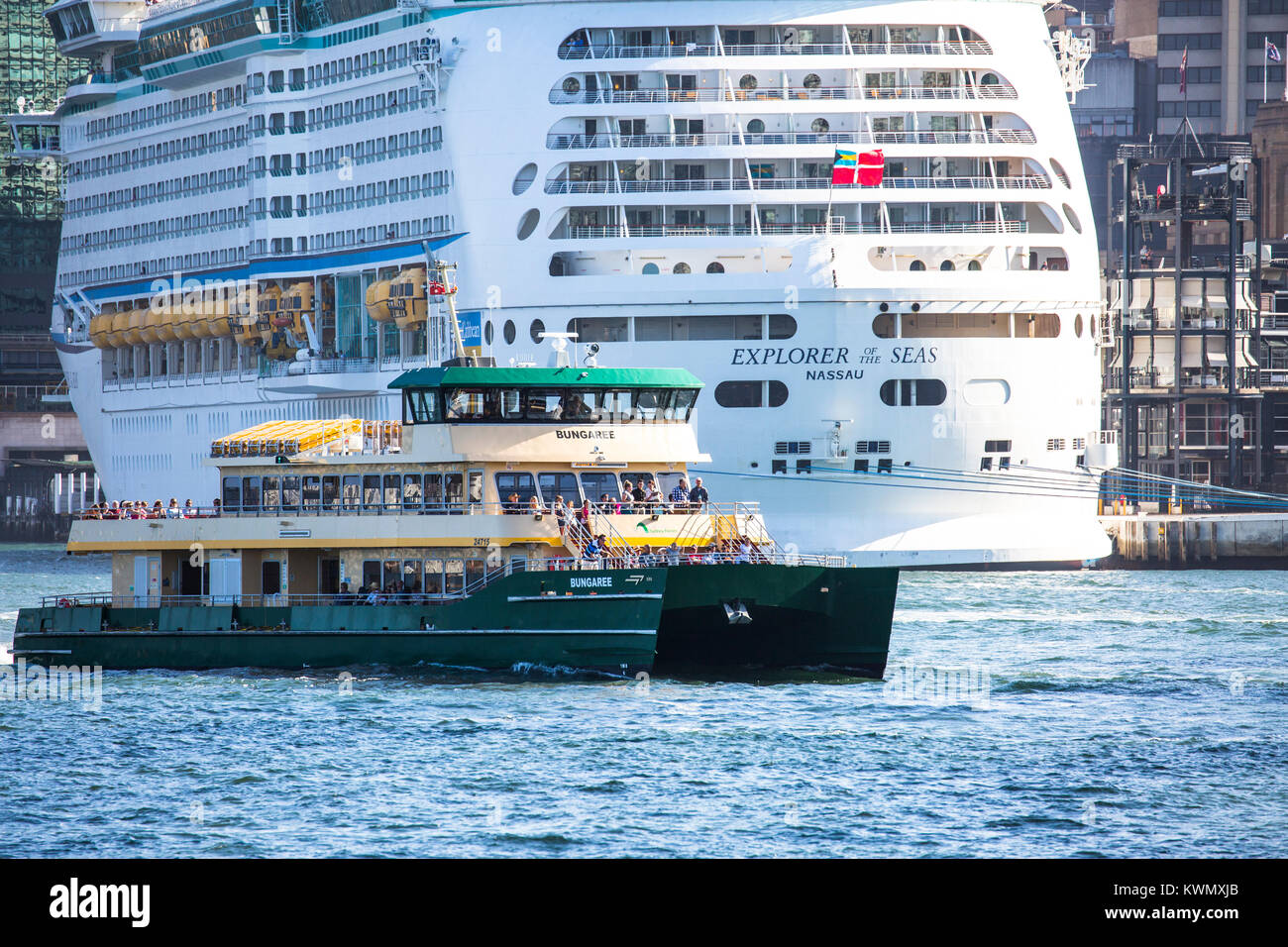 Sydney ferry passes by cruise ship Explorer of the Seas moored in Sydney harbour,Sydney,Australia - Stock Image