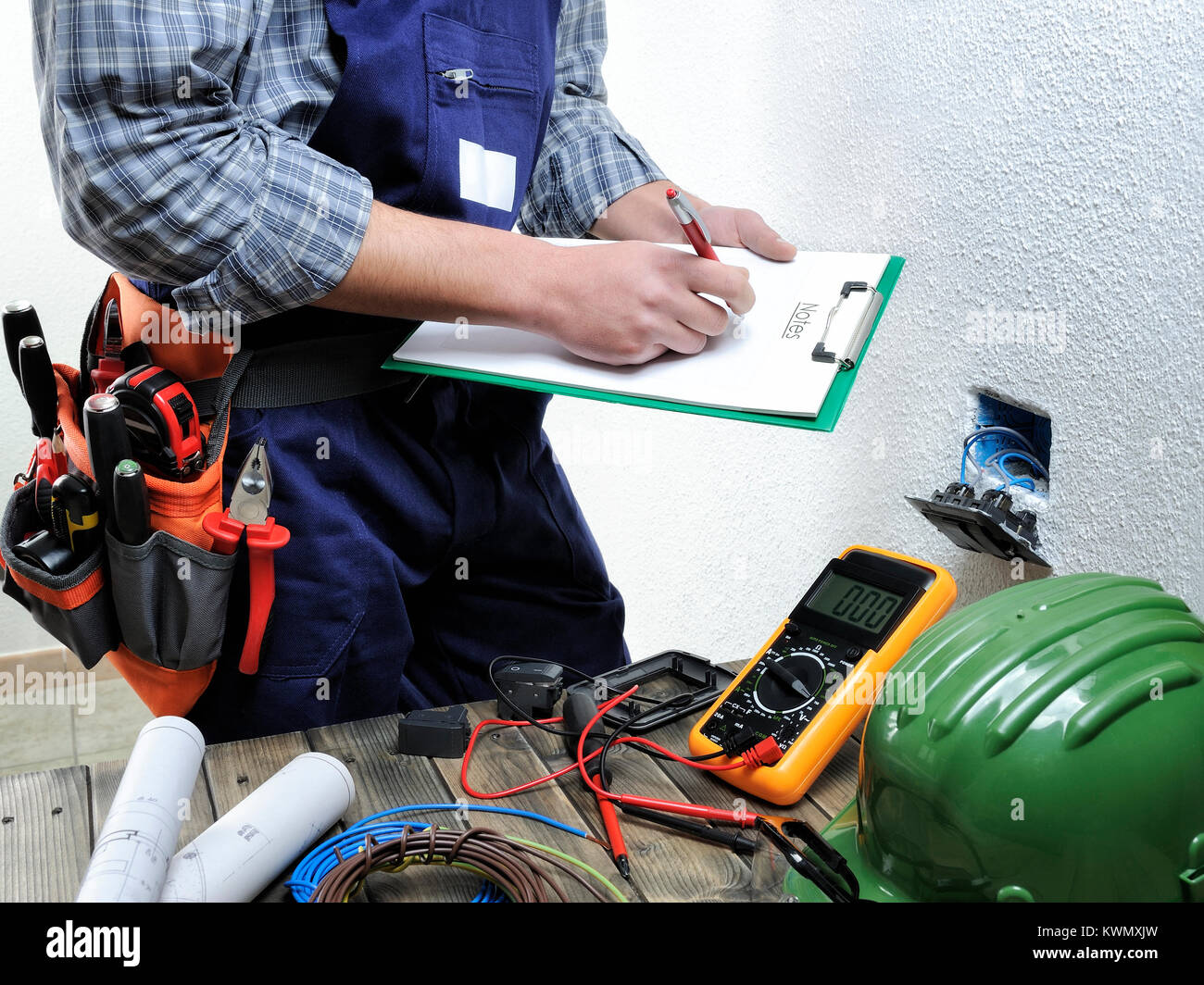 Young electrician at work on switches and sockets of a residential ...