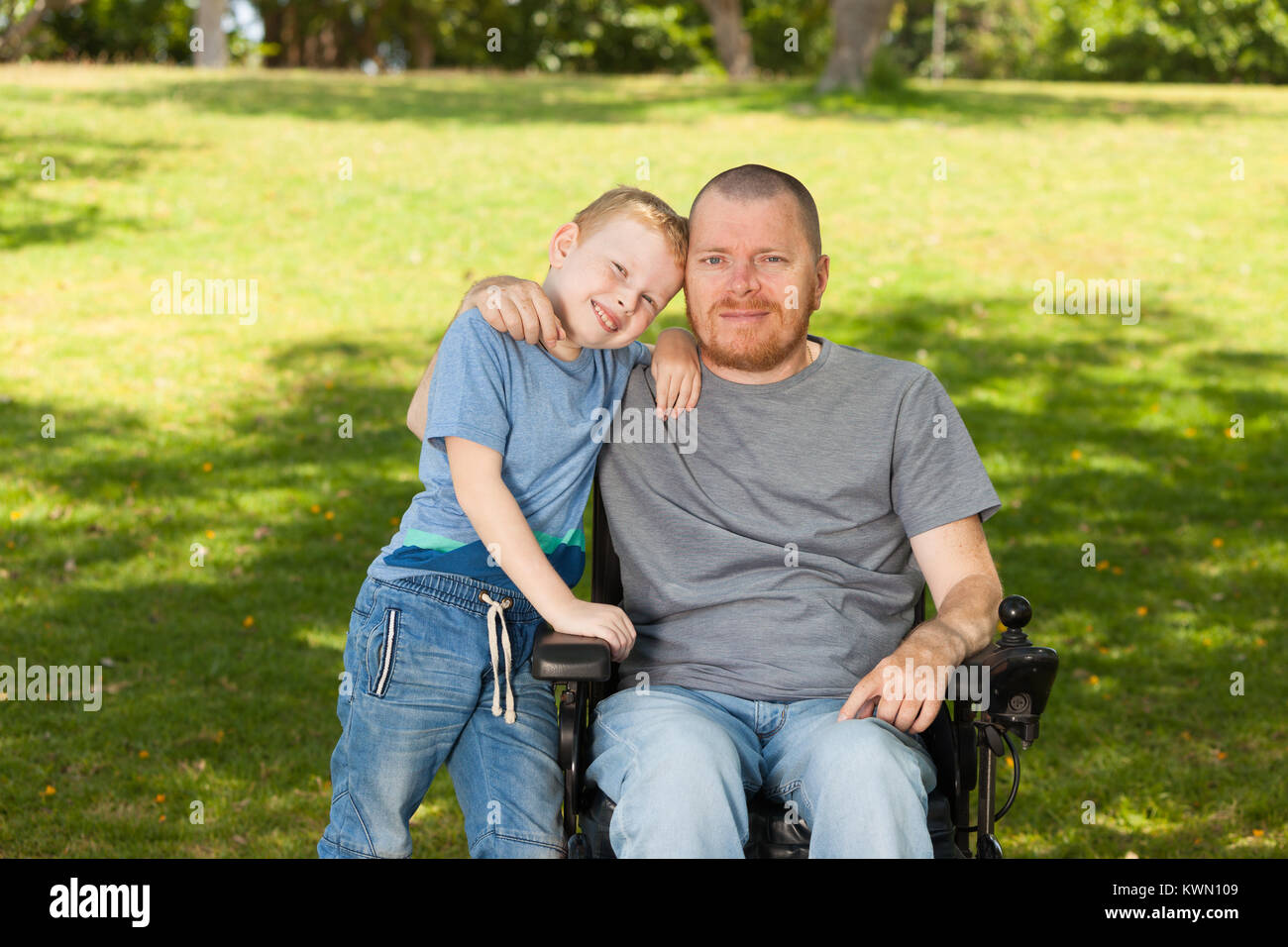 Disabled father with his little son. - Stock Image