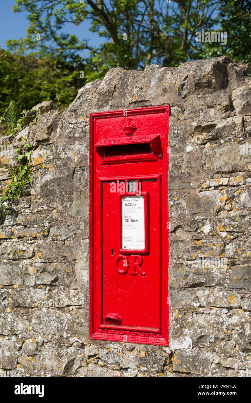 Red post Box built into the stone wall, Combrook, Warwickshire, England, UK - Stock Image