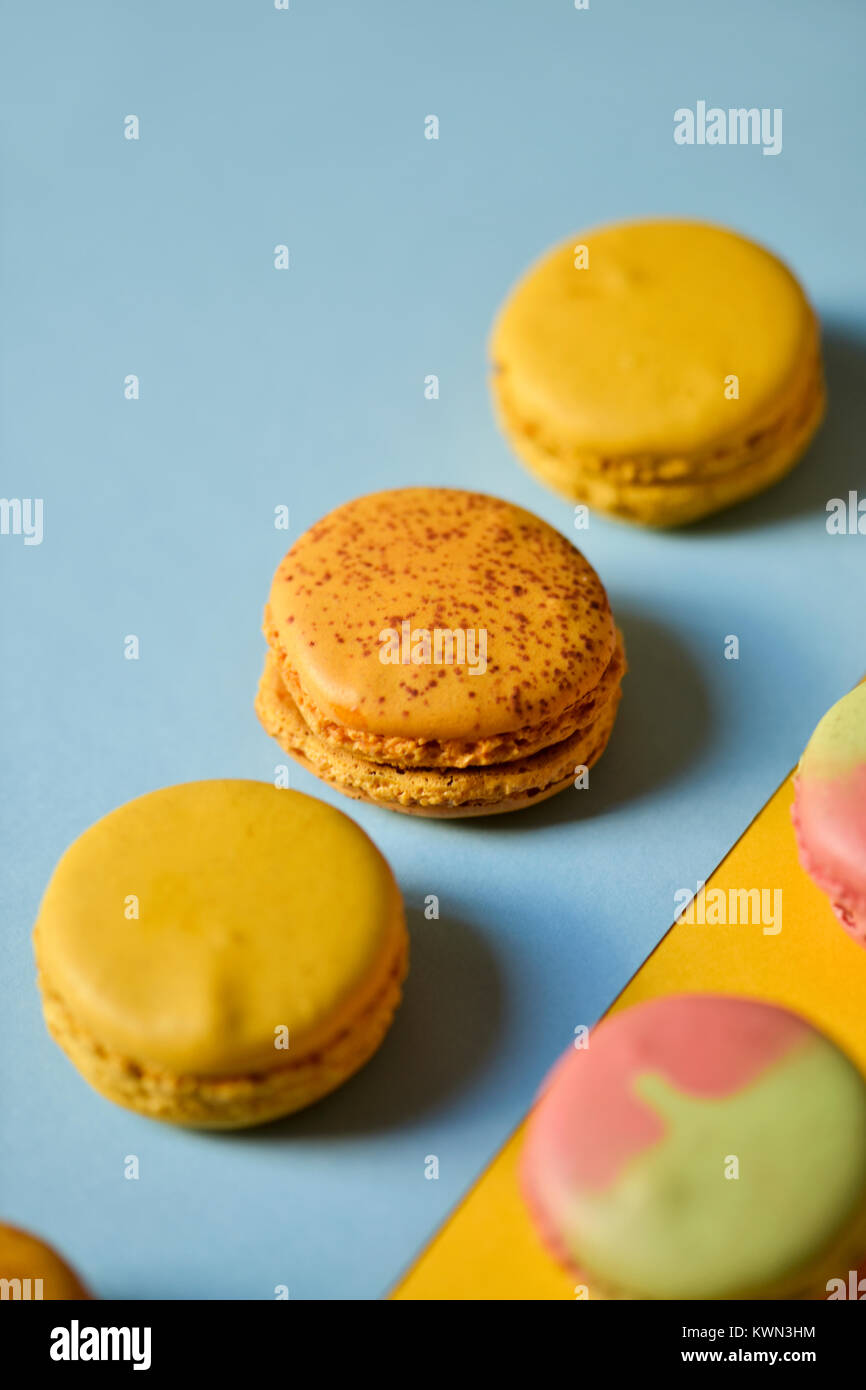 some delicious macarons of different flavors on a blue and orange background - Stock Image