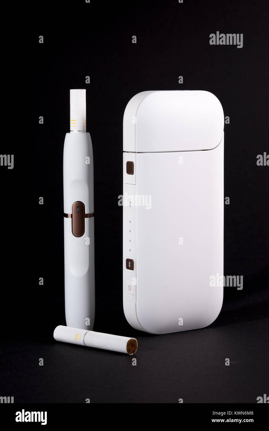Newest electronic cigarettes, heating tobacco system IQOS, smoking, white isolated on black background - Stock Image