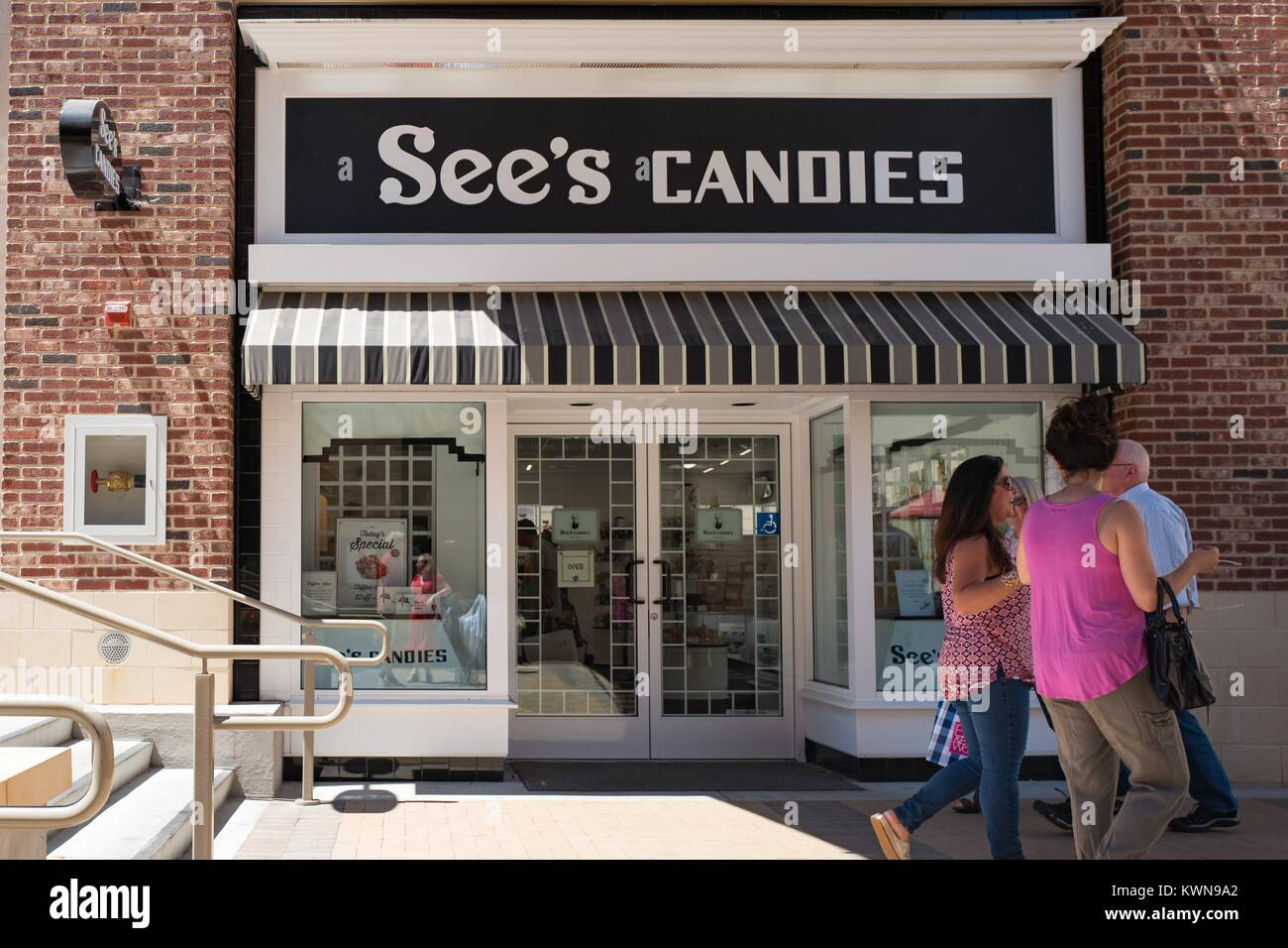 Shoppers walk past the facade of See's Candies in the upscale Broadway Plaza shopping center in Walnut Creek, - Stock Image
