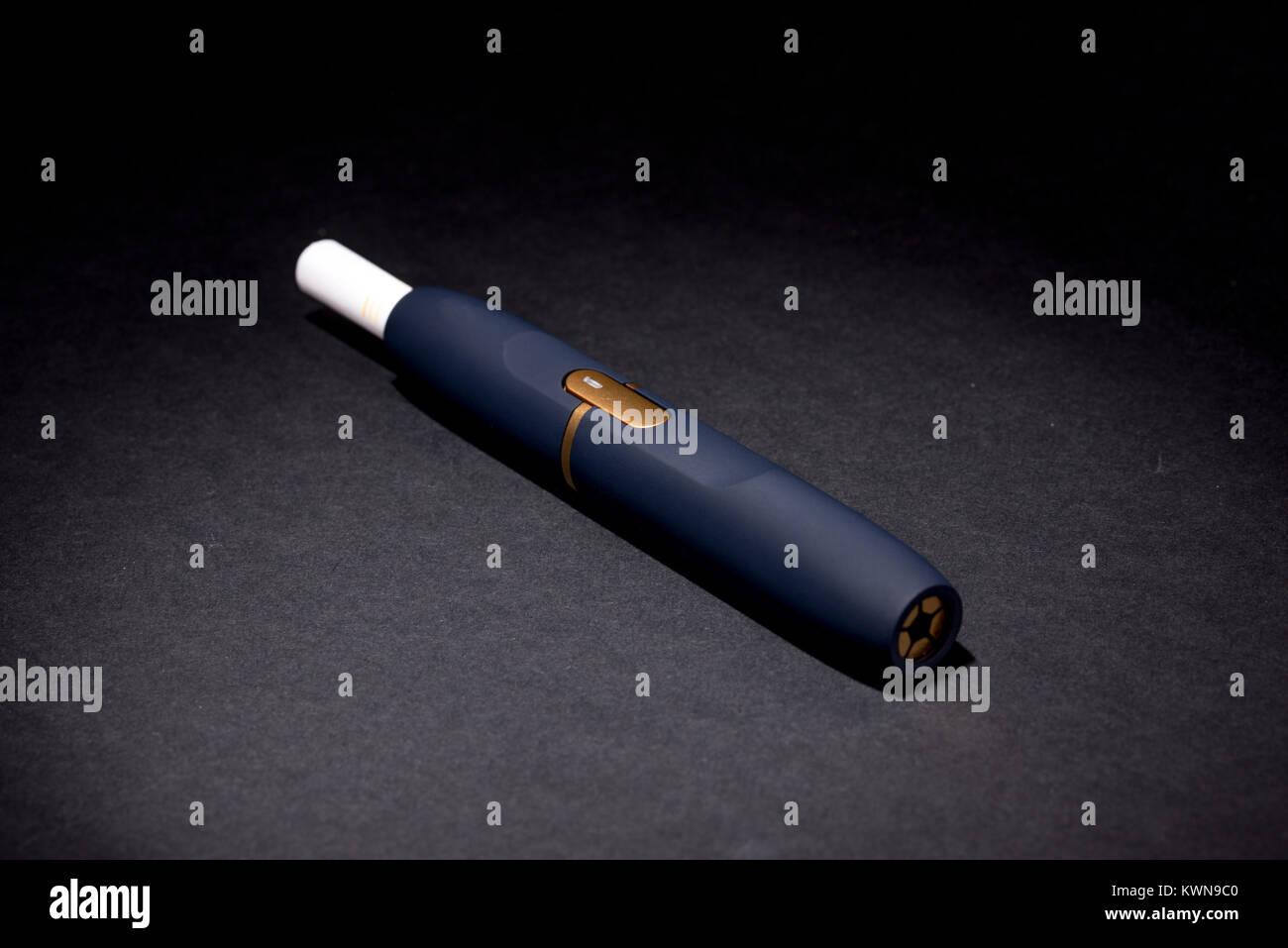 Newest electronic cigarettes, heating tobacco system IQOS, smoking, dark blue isolated on black background - Stock Image