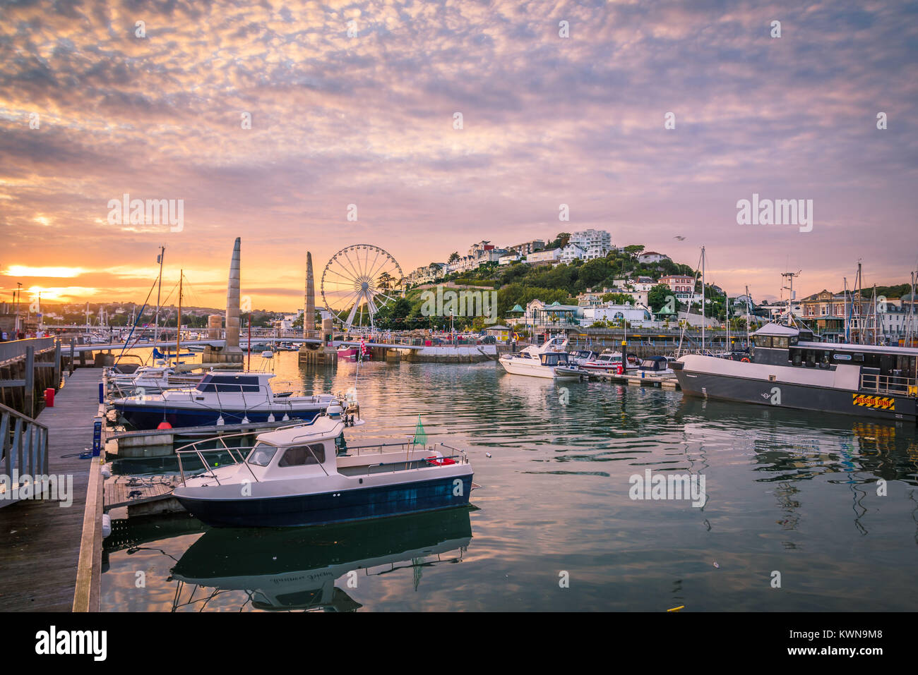 Torquay harbour at sunset. Panoramic view of the popular seaside resort town during a colorful sunset. Devon, England - Stock Image