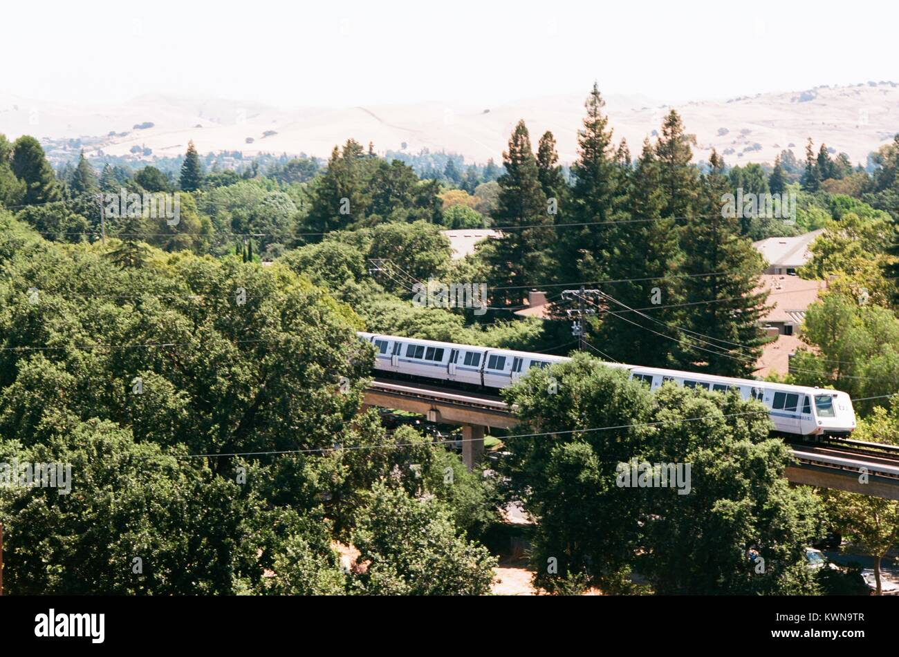 A Bay Area Rapid Transit (BART) train is seen passing through trees and the Diablo Foothills in downtown Walnut - Stock Image