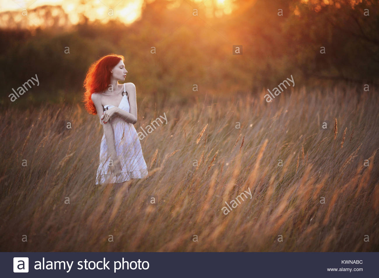 A woman with red curly hair in white sundress on background of dawn. Red-haired girl with pale skin, bright unusual - Stock Image