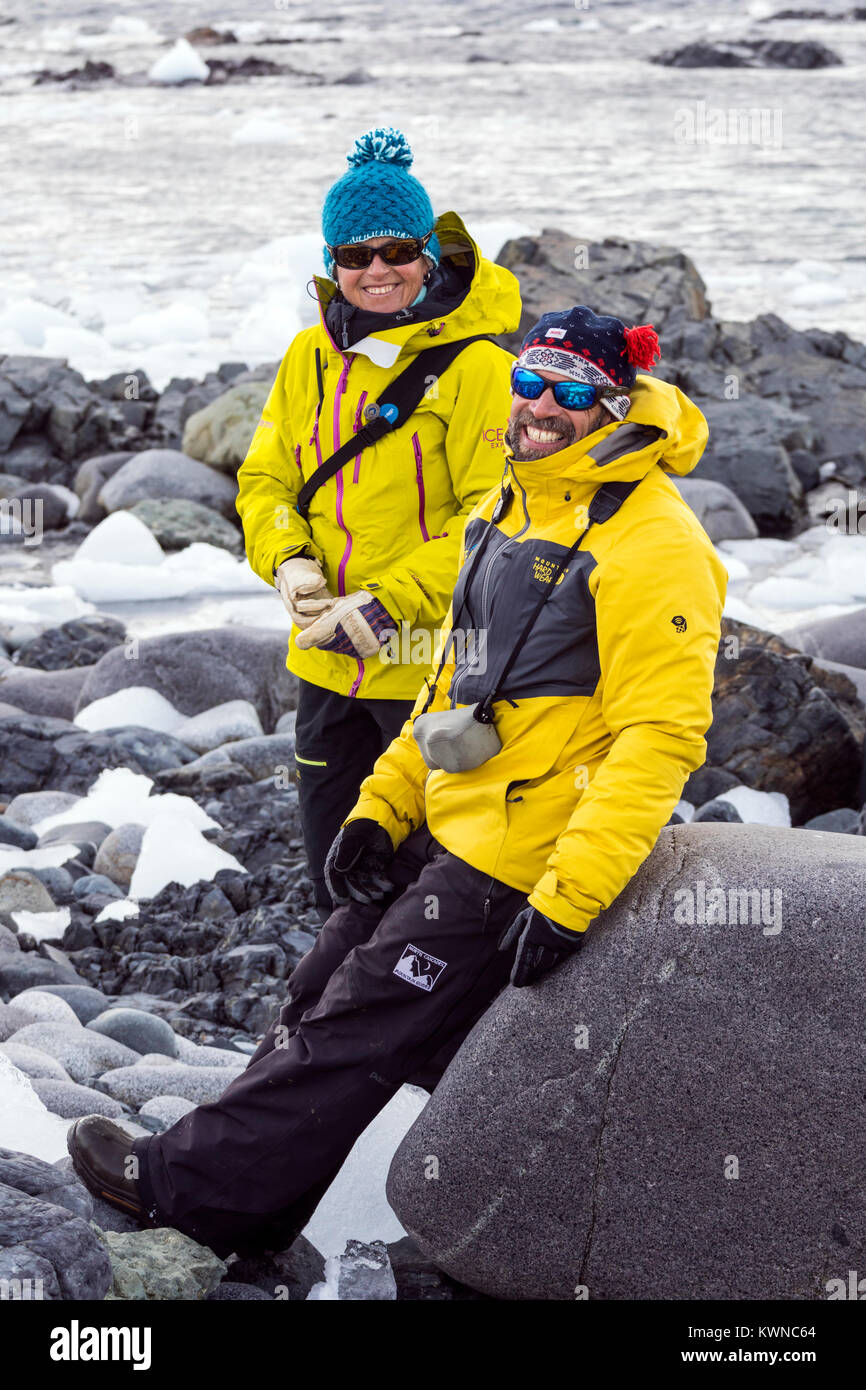 Two profesional mountain guides chat on rocky beach; Half Moon Island; Antarctica - Stock Image