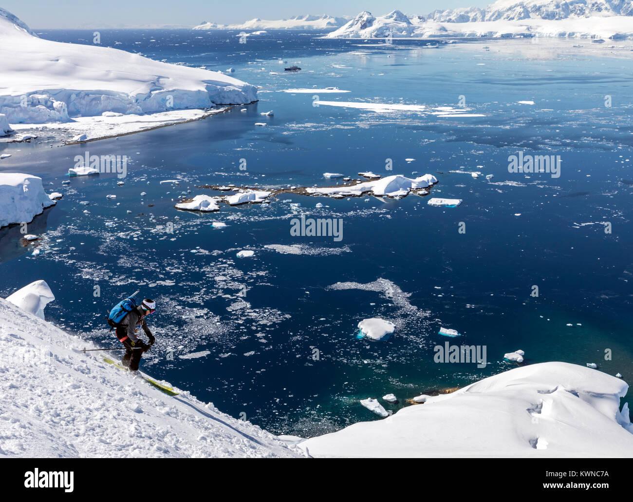 Alpine ski mountaineer skiing downhill in Antarctica; Nansen Island - Stock Image