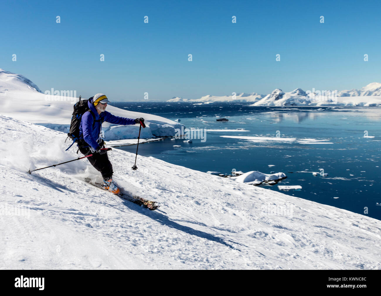 Alpine ski mountaineers skiing downhill; Nansen Island; Antarctica - Stock Image