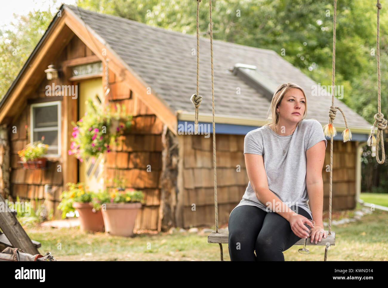 millenial woman sitting in backyard on swing with glass of wine thinking - Stock Image