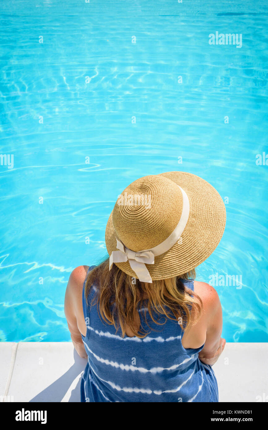 overhead view of woman in straw summer hat sitting at edge of pool with feet in water - Stock Image
