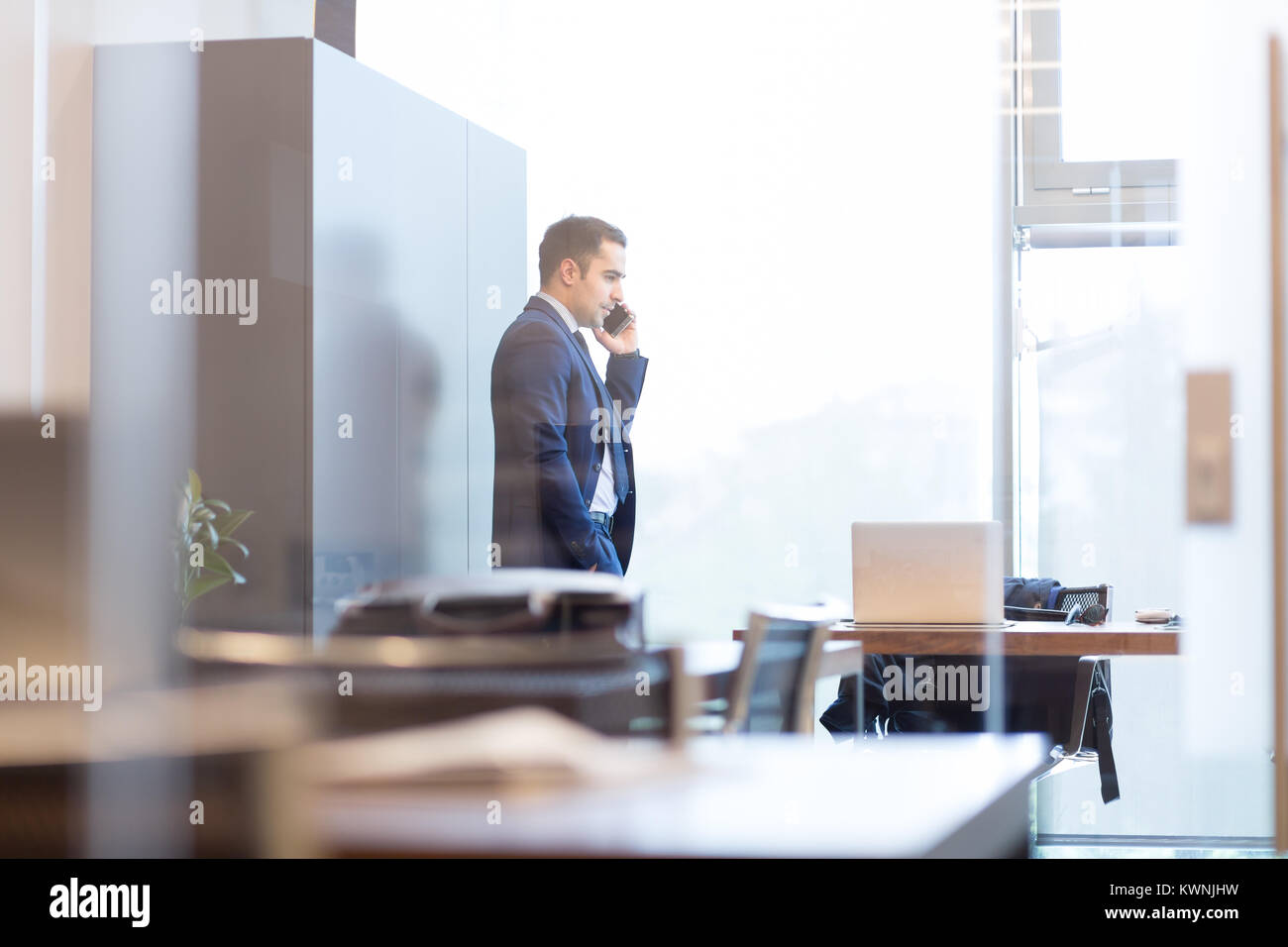 Businessman talking on a mobile phone while looking through window. - Stock Image