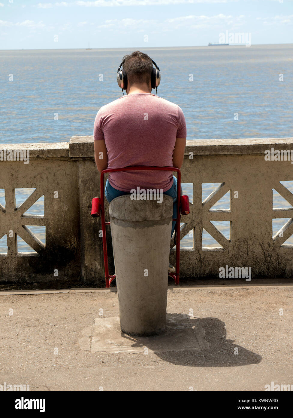 Rear view of seated man listening to music along coast near Aeroparque Jorge Newbery; Buenos Aires; Argentina - Stock Image