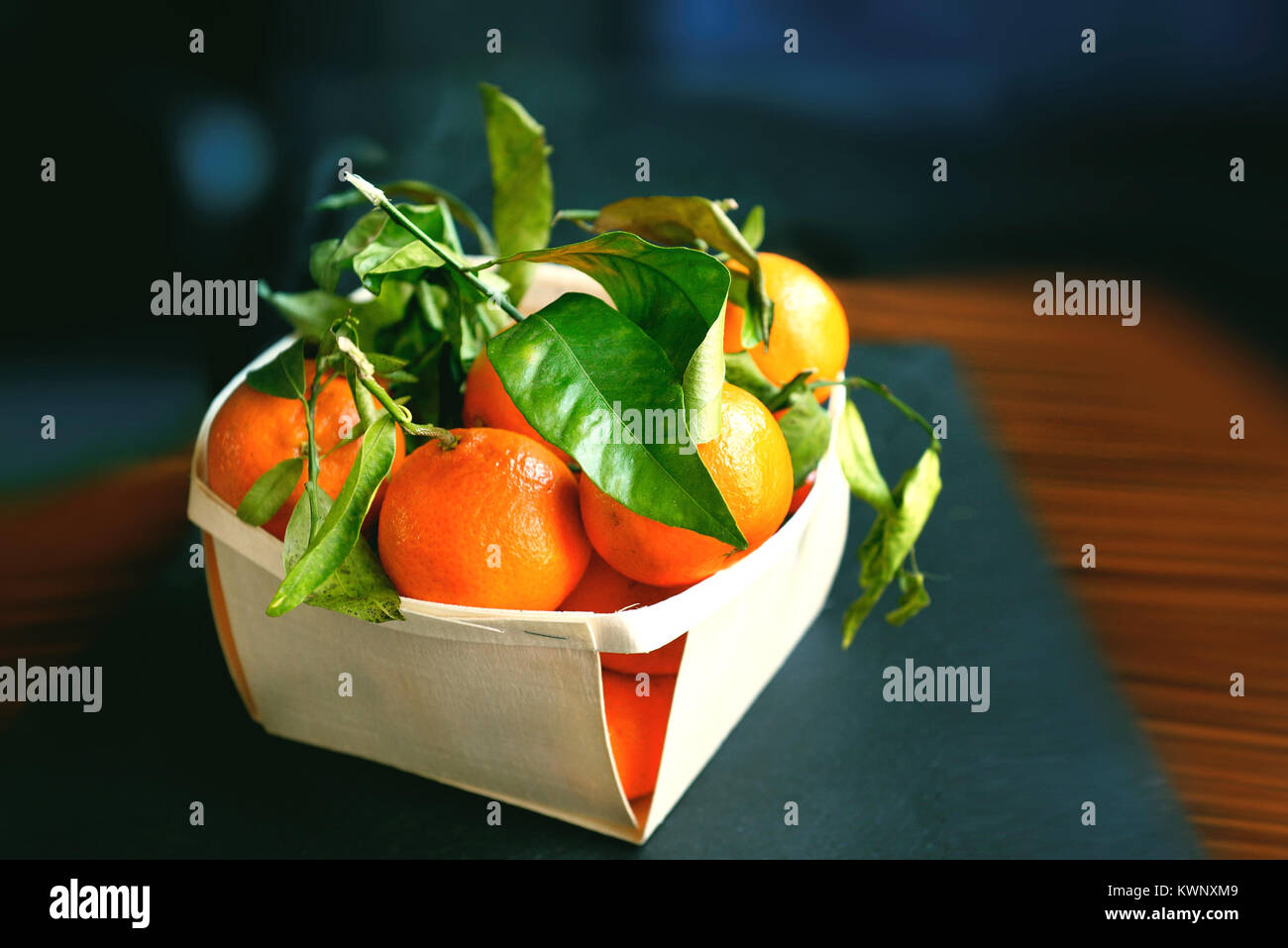 Tangerines  or oranges, mandarins, clementines, citrus fruits with lgreen eaves in basket over rustic wooden background. - Stock Image