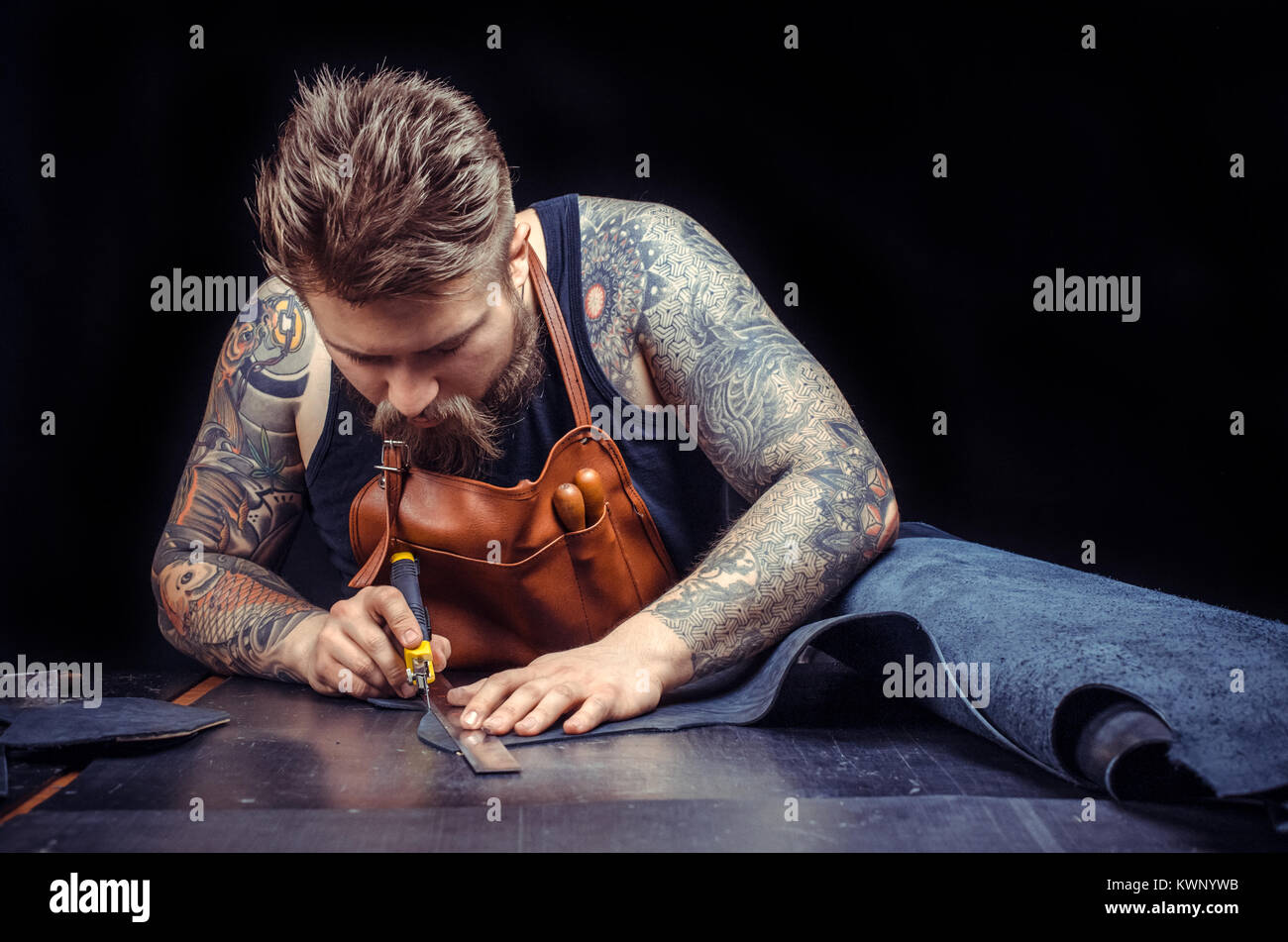 Man working with leather processes a workpiece from leather in the place of work - Stock Image