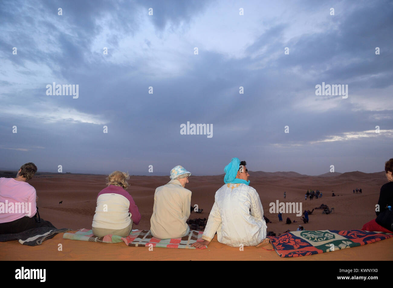 Tourists and  Berbers watching the sunrise on a camel excursion to the sand dunes at Merzouga, Morocco, North Africa - Stock Image