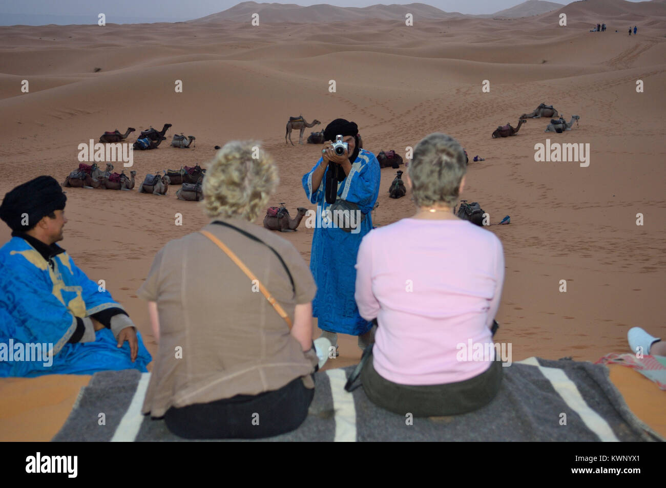 Tourists having their photograph taken by a Berber guide on a camel excursion to the sand dunes at Merzouga, Morocco, - Stock Image