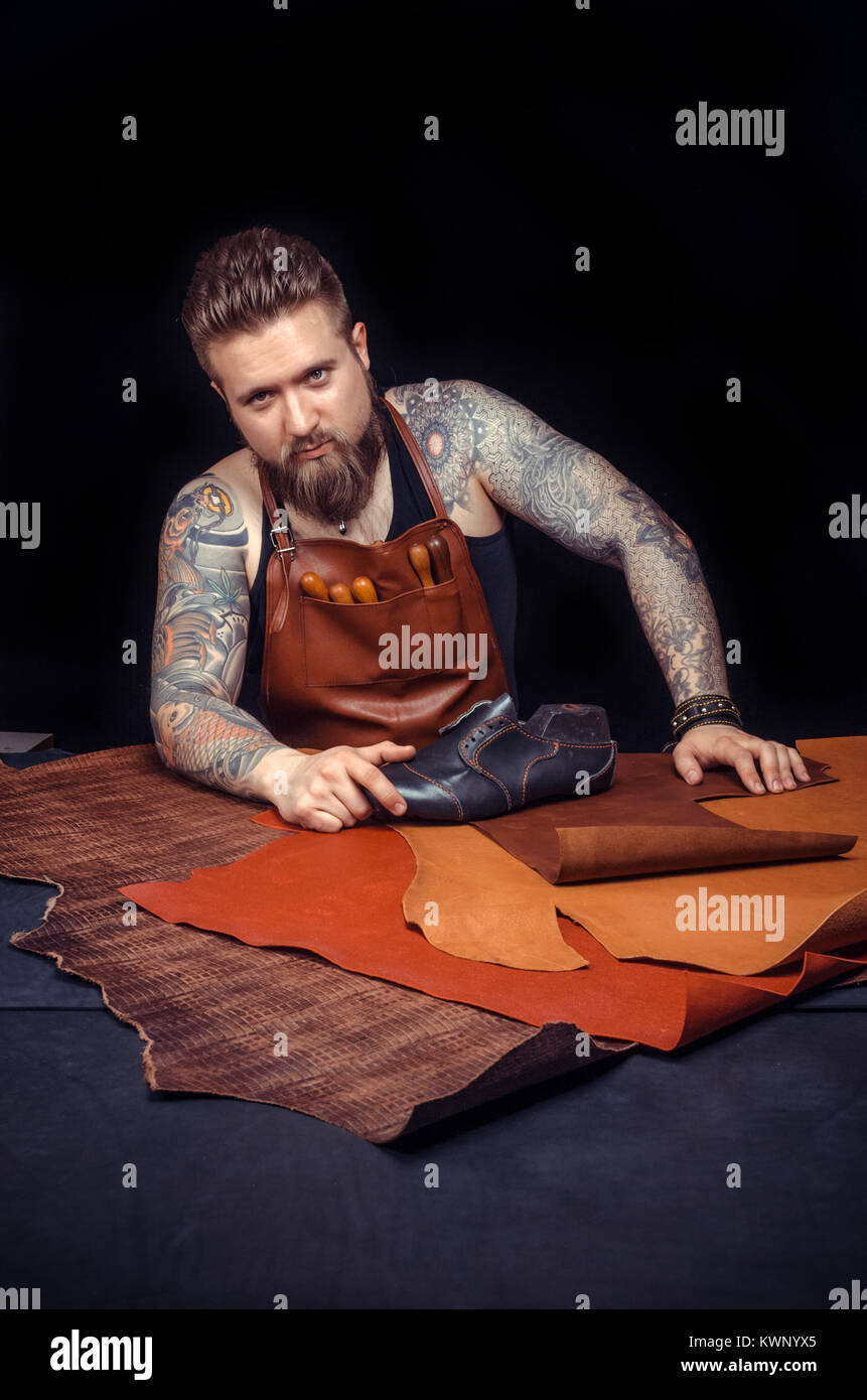 Leather Professional works with leatherwork in the place of work - Stock Image