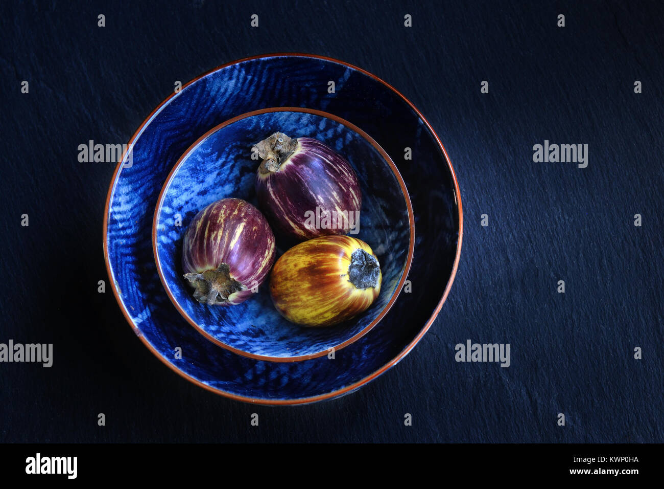 Healthy and fresh purple eggplants in a bwols over dark stone background. Vegetarian food, health or cooking concept, - Stock Image