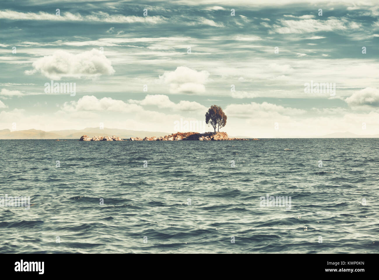 Lonely island on the lake. View of the Titicaca Lake on the border of Peru and Bolivia. Vintage filter applied. - Stock Image