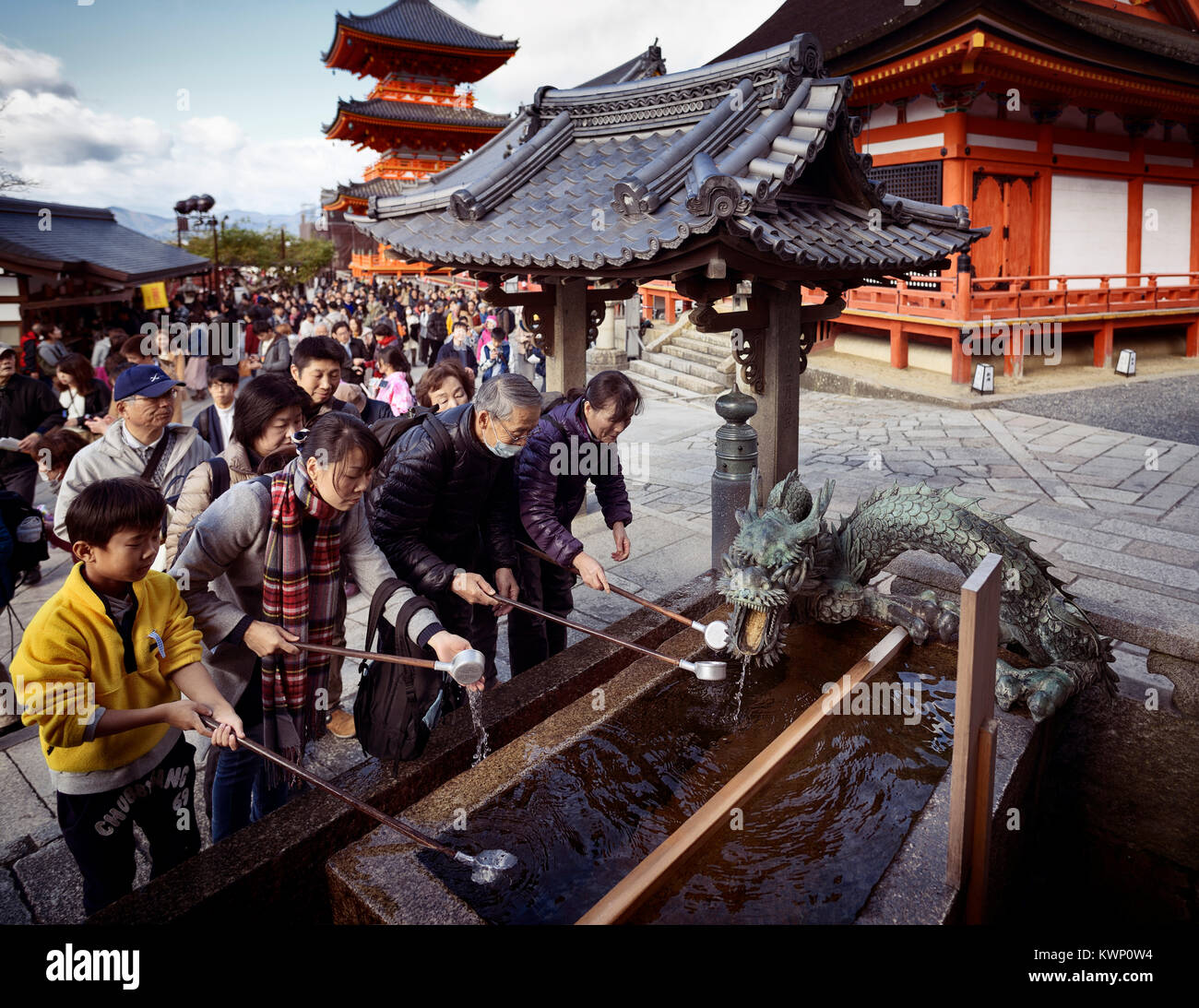 People washing hands and mouth at chozubachi, water ablution pavilion, basin for a cleansing ritual, chozuya or - Stock Image