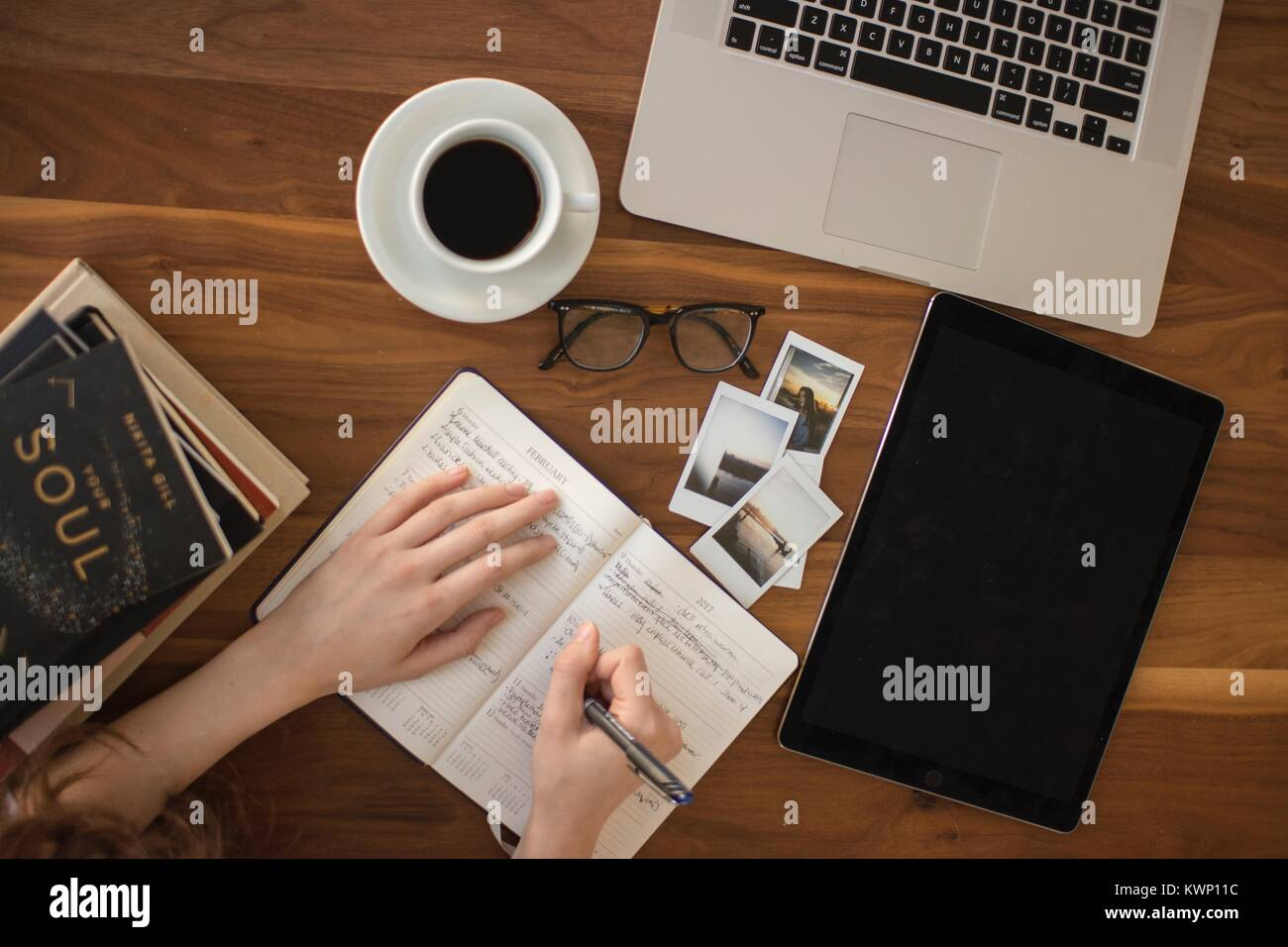 Millennial writing in a travel journal - Stock Image