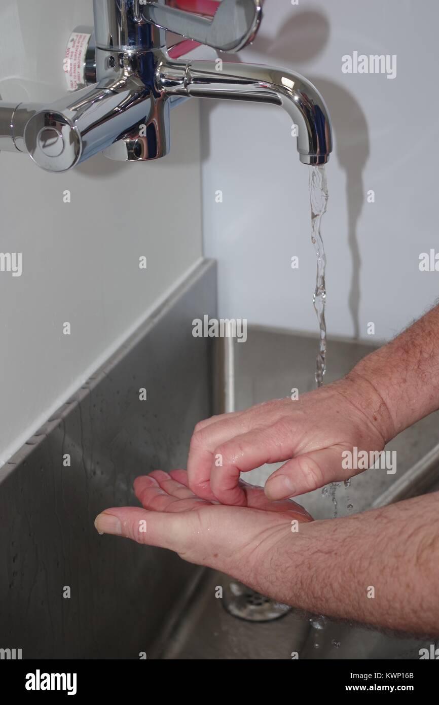 Surgeon Washing Hands in Modern British Hospital Operating Theatre. - Stock Image