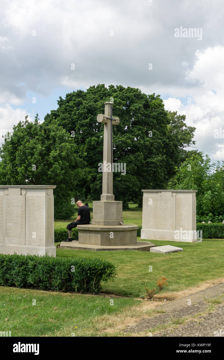 A man dressed in black sits in quiet contemplation by a war memorial; Billing Road Cemetery, Northampton, UK - Stock Image