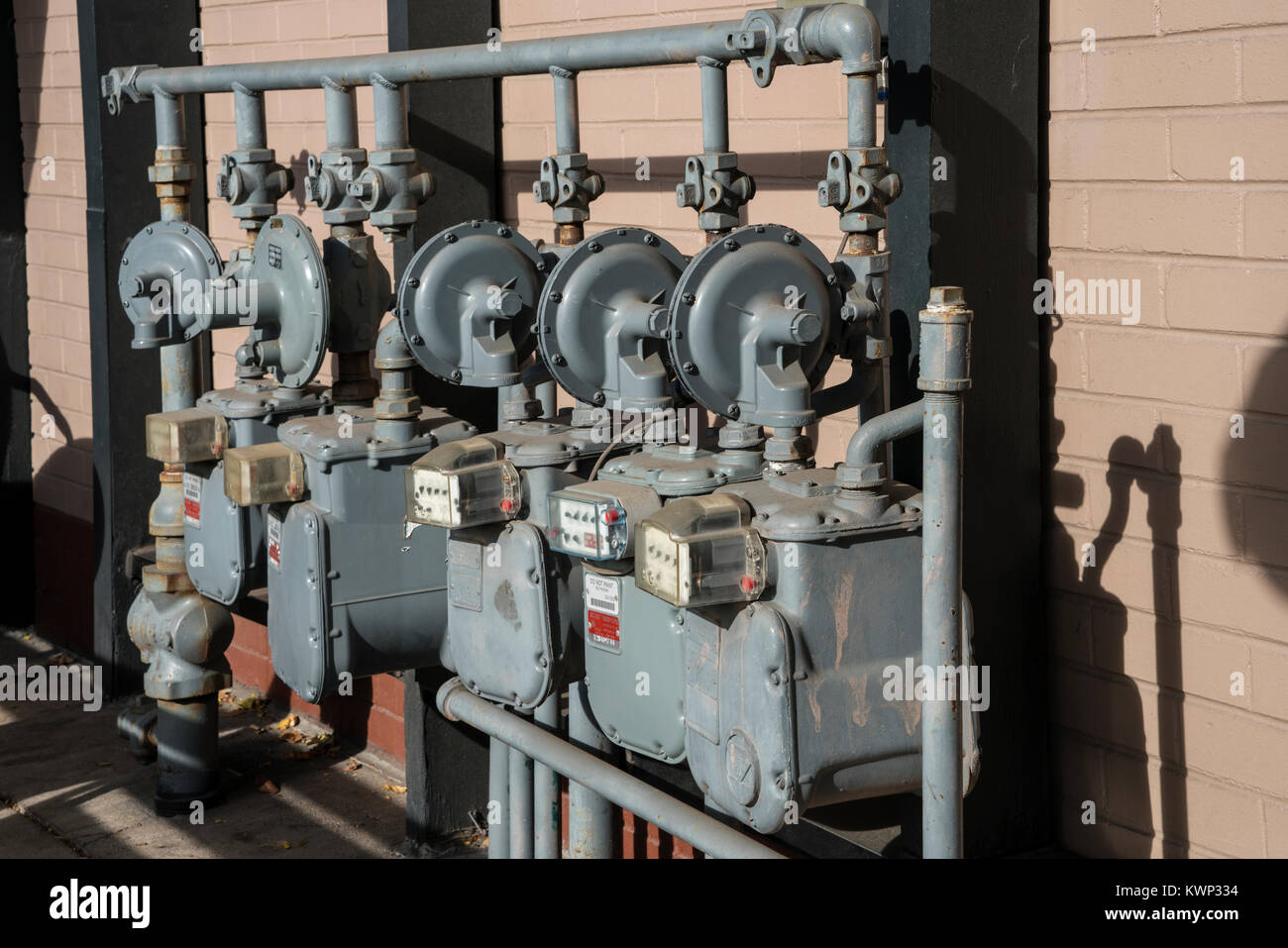 multiple gray gas meters besides building Stock Photo