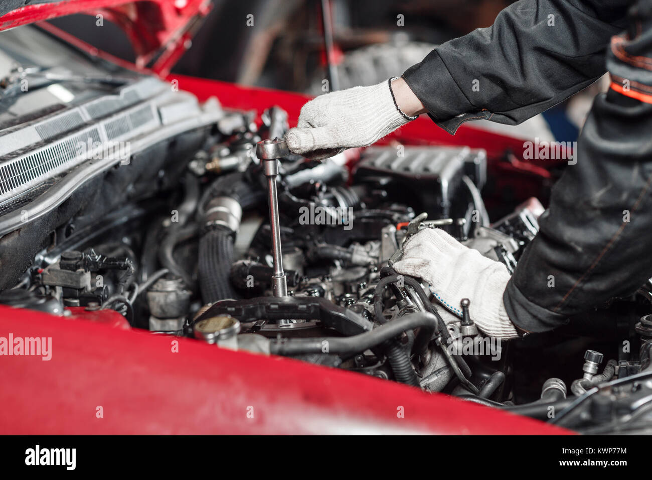 Repairing of modern diesel engine, workers hands and tool. Close-up of an auto mechanic working on a car motor - Stock Image