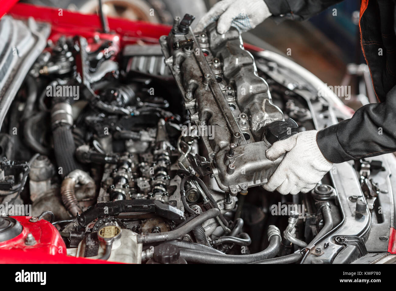 Repairing of modern diesel engine, workers hands and tool. Car mechanic looking at engine for analysis symptoms - Stock Image