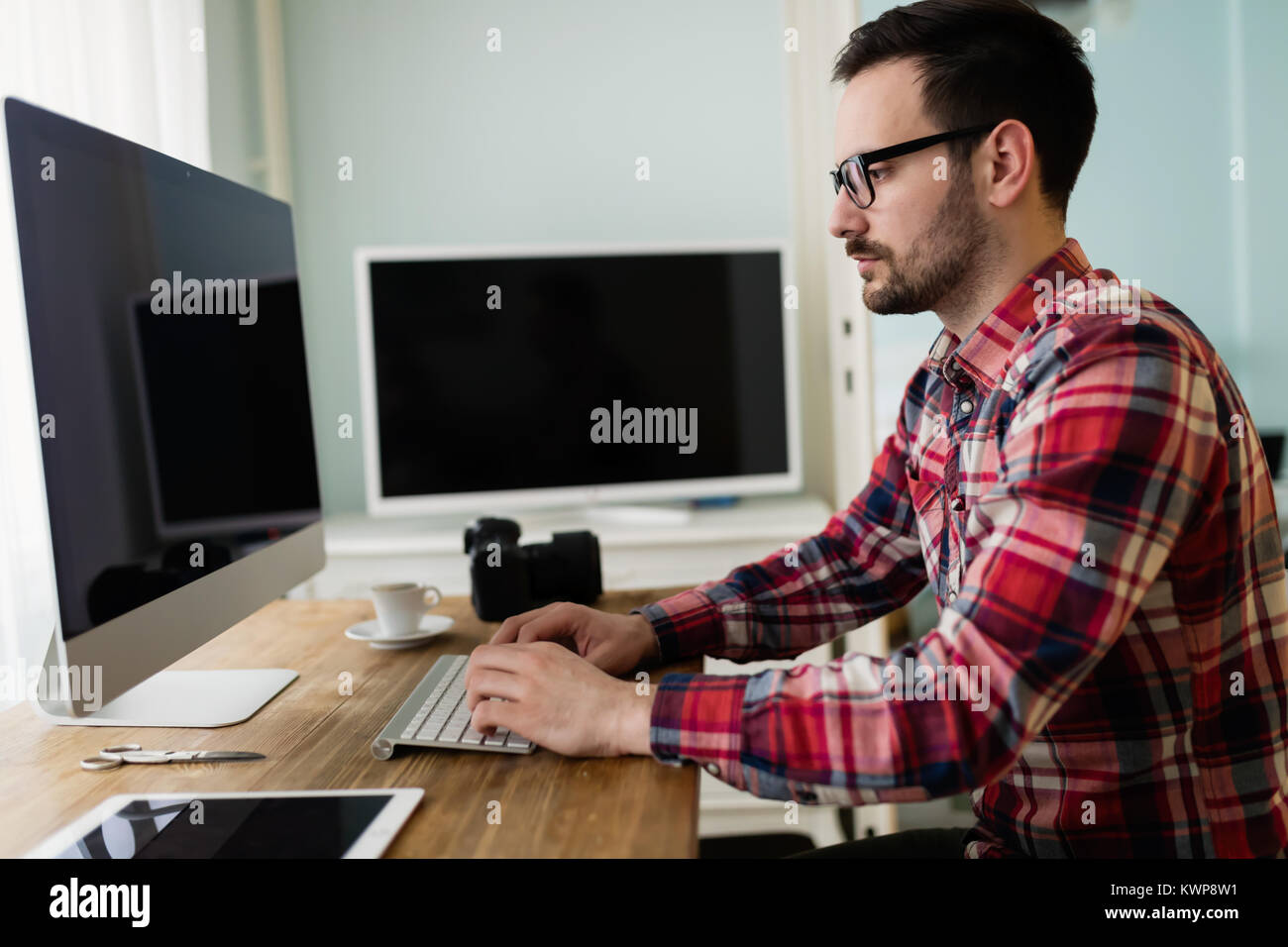 Young handsome designer working on project on computer - Stock Image
