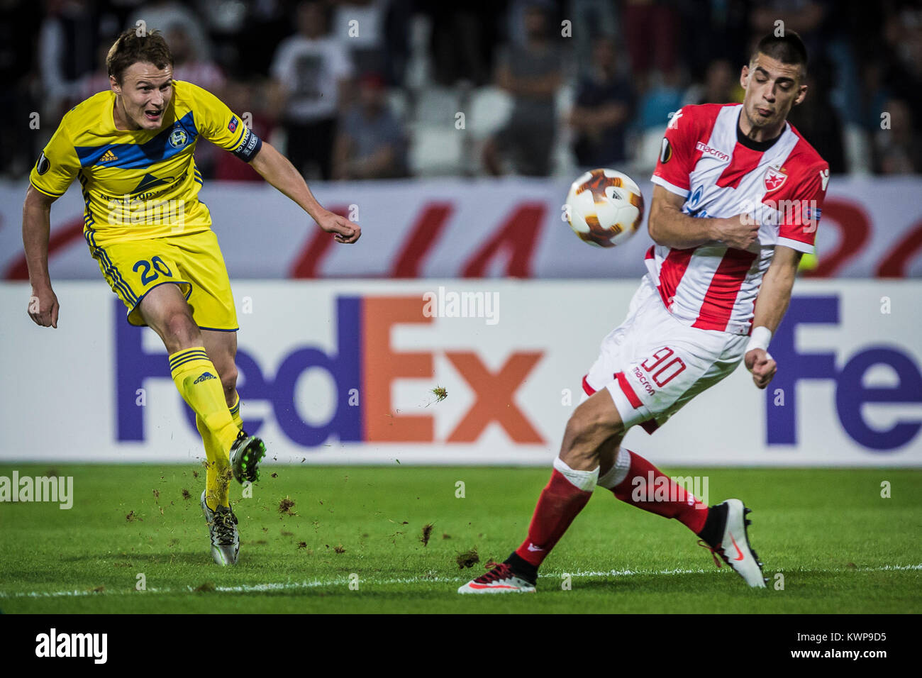 Forward Vitali Rodionov of FC BATE Borisov shoots on the goal past the attamepted block from Vujadin Savić - Stock Image