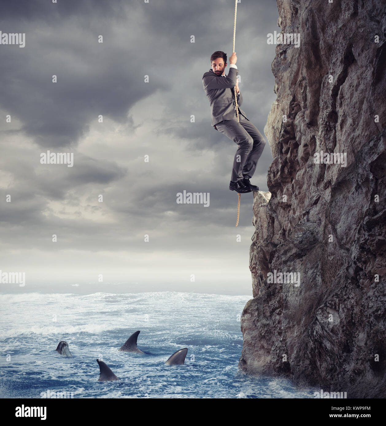 Businessman is likely to fall into the sea with sharks. concept of problems and difficulty in business Stock Photo