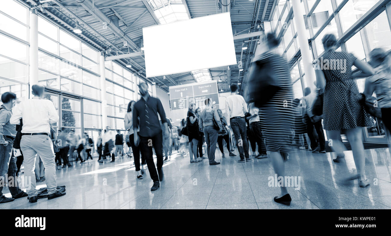 crowd of people rushing in trade show hall, including copy space banner. ideal for websites and magazines layouts Stock Photo