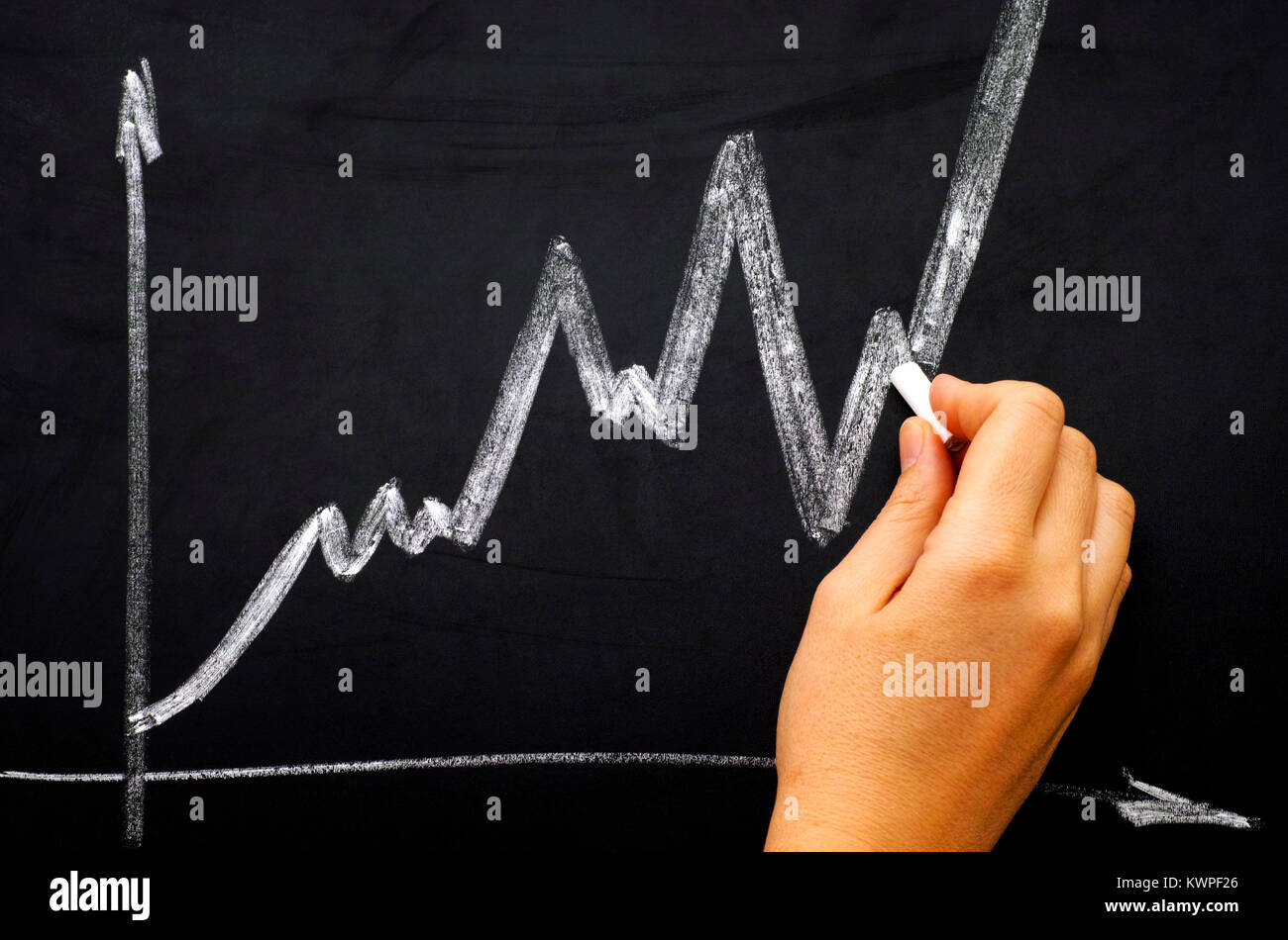 Woman hand with chalk drawing graph on chalk board. - Stock Image