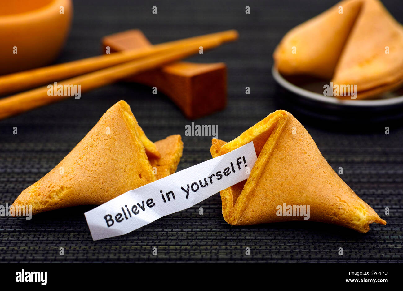 Paper strip with phrase Believe in yourself from fortune cookie, another cookie and chopsticks on black napkin background. - Stock Image