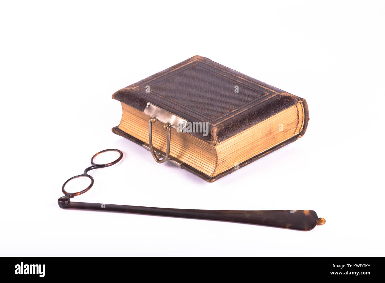 antique eye glasses and book ove a white background - Stock Image