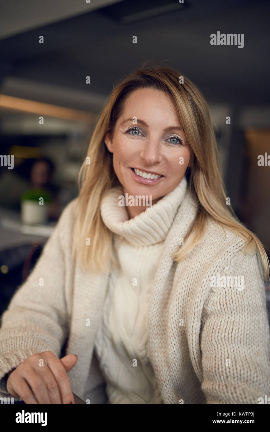 Attractive blond woman smiling at the camera while enjoying a glass of wine indoors at a pub or restaurant - Stock Image