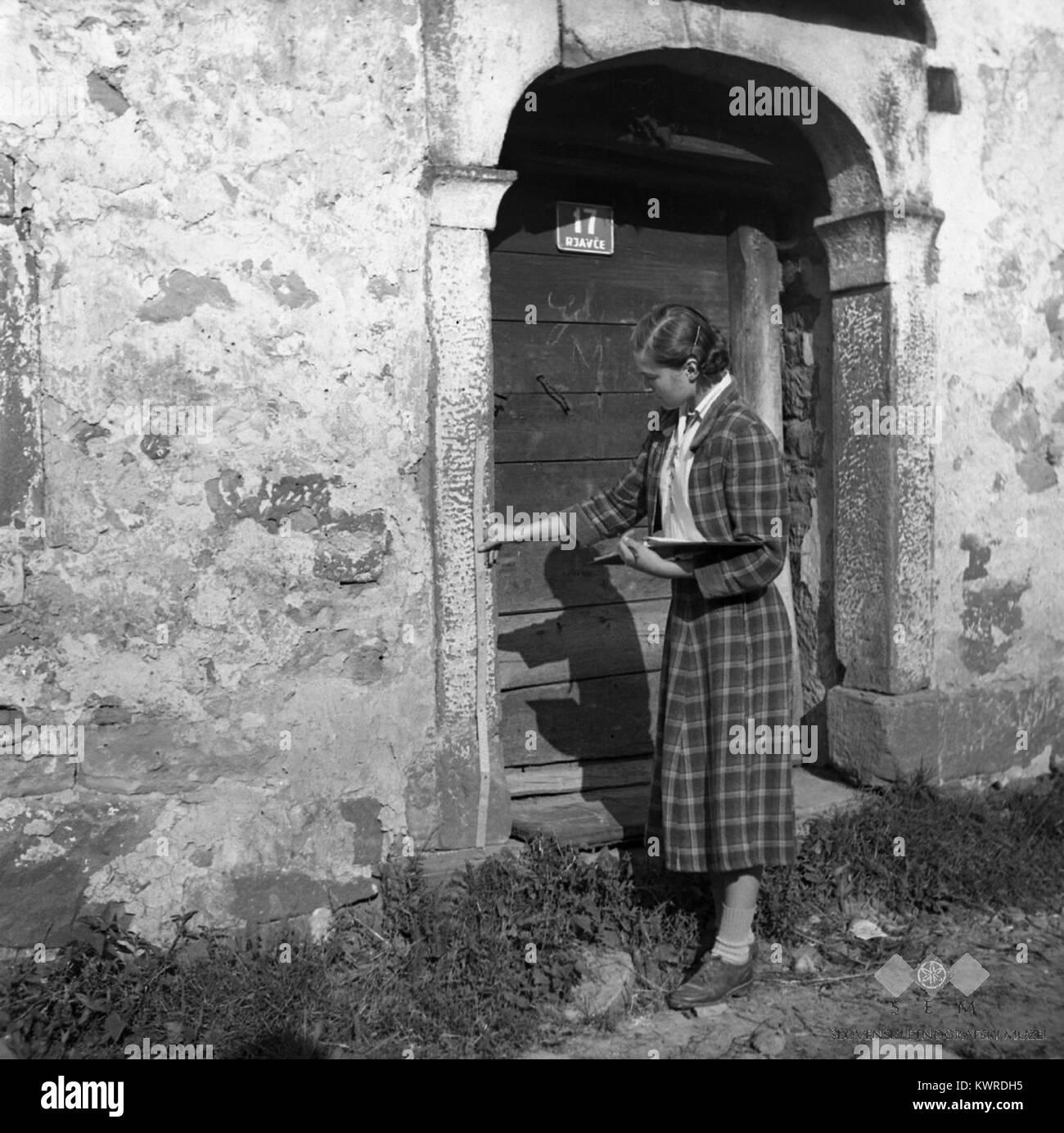 Članica ekipe Sibila Nekrep meri vrata pri hiši Rjavče 1955 - Stock Image