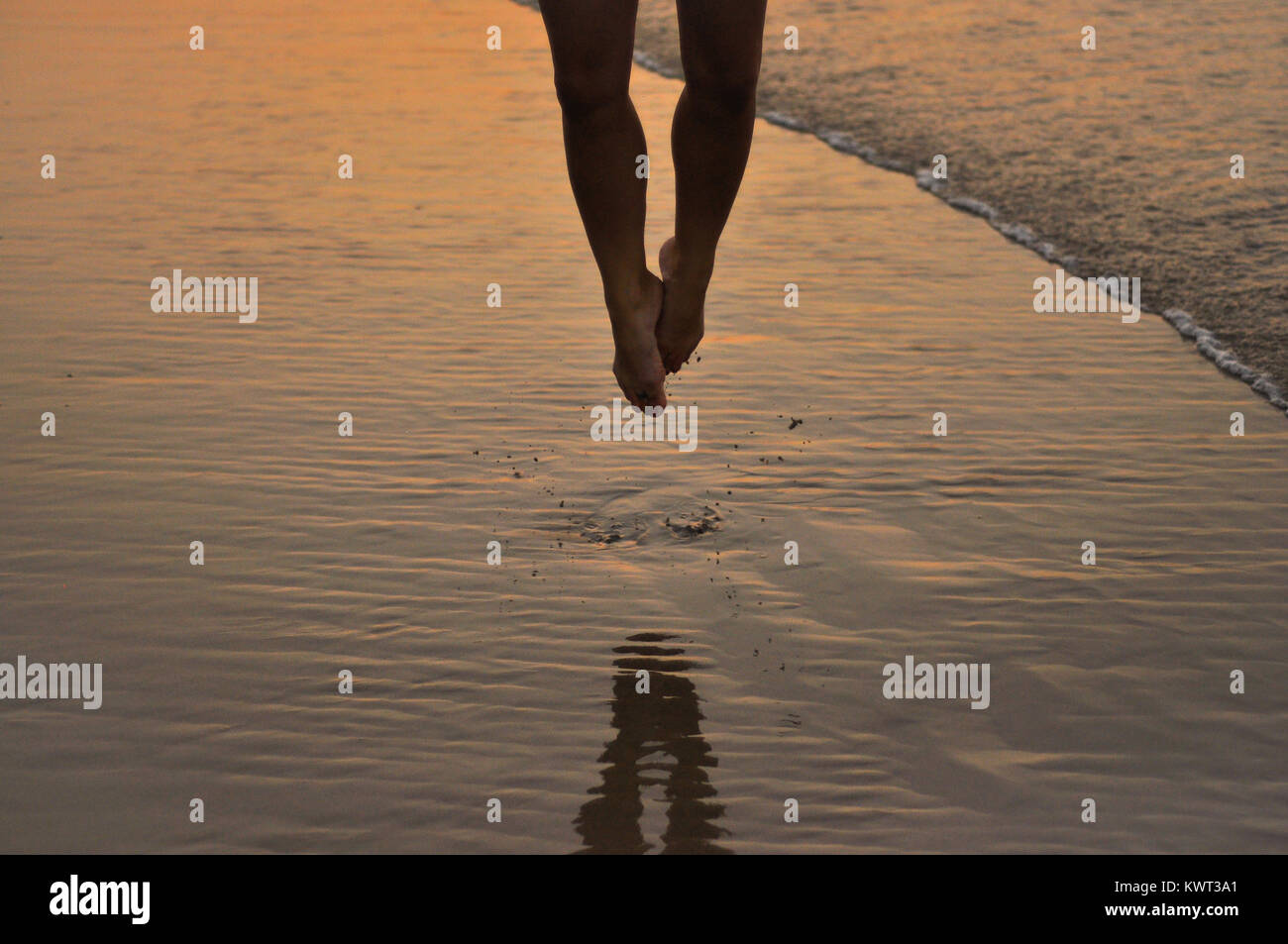 Lower body of a woman jumping on the sand - Stock Image