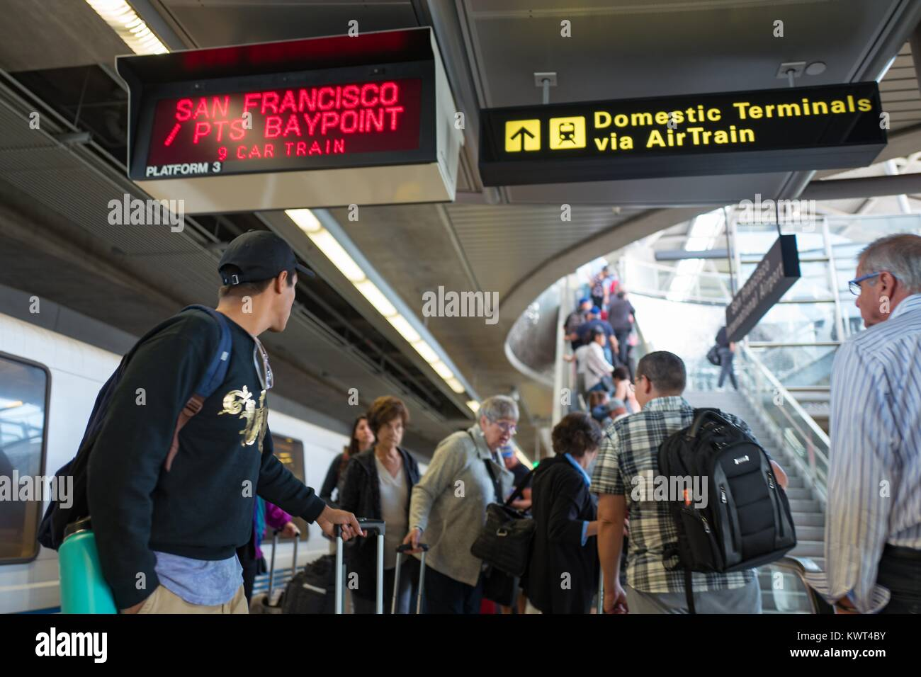 A large crowd of passengers exits a Bay Area Rapid Transit (BART) train at San Francisco International Airport (SFO) - Stock Image