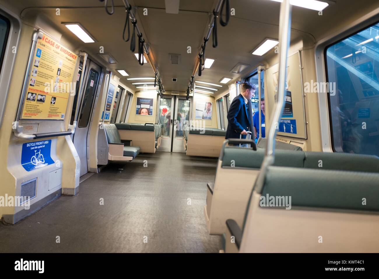 A man in a business suit exits a Bay Area Rapid Transit (BART) light rail train at San Francisco International Airport, - Stock Image
